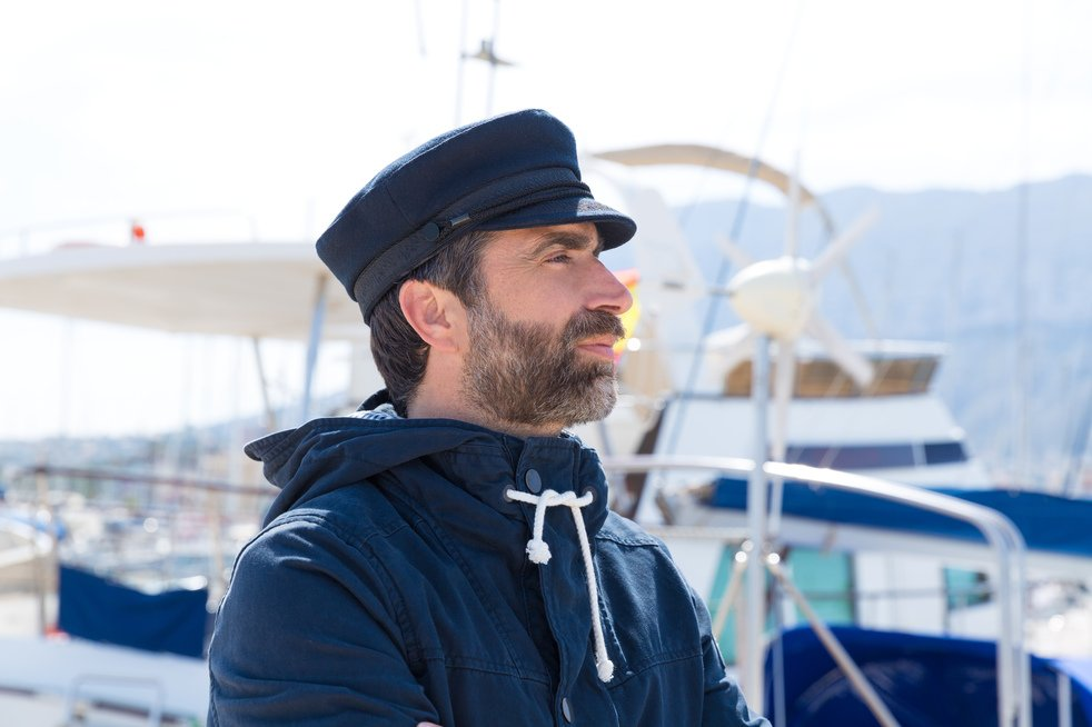Sailor man in marina port with boats background and blue cap