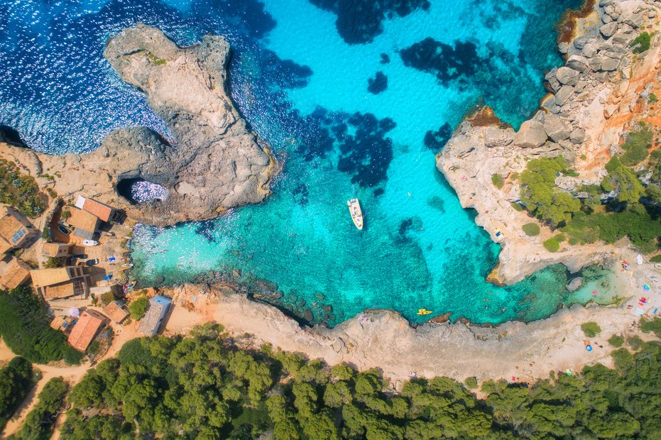 Aerial view of clear sea with blue water, sandy beach, rocks, green trees, yachts and boats in sunny morning in summer. Travel in Mallorca, Balearic islands, Spain. Top view. Colorful landscape