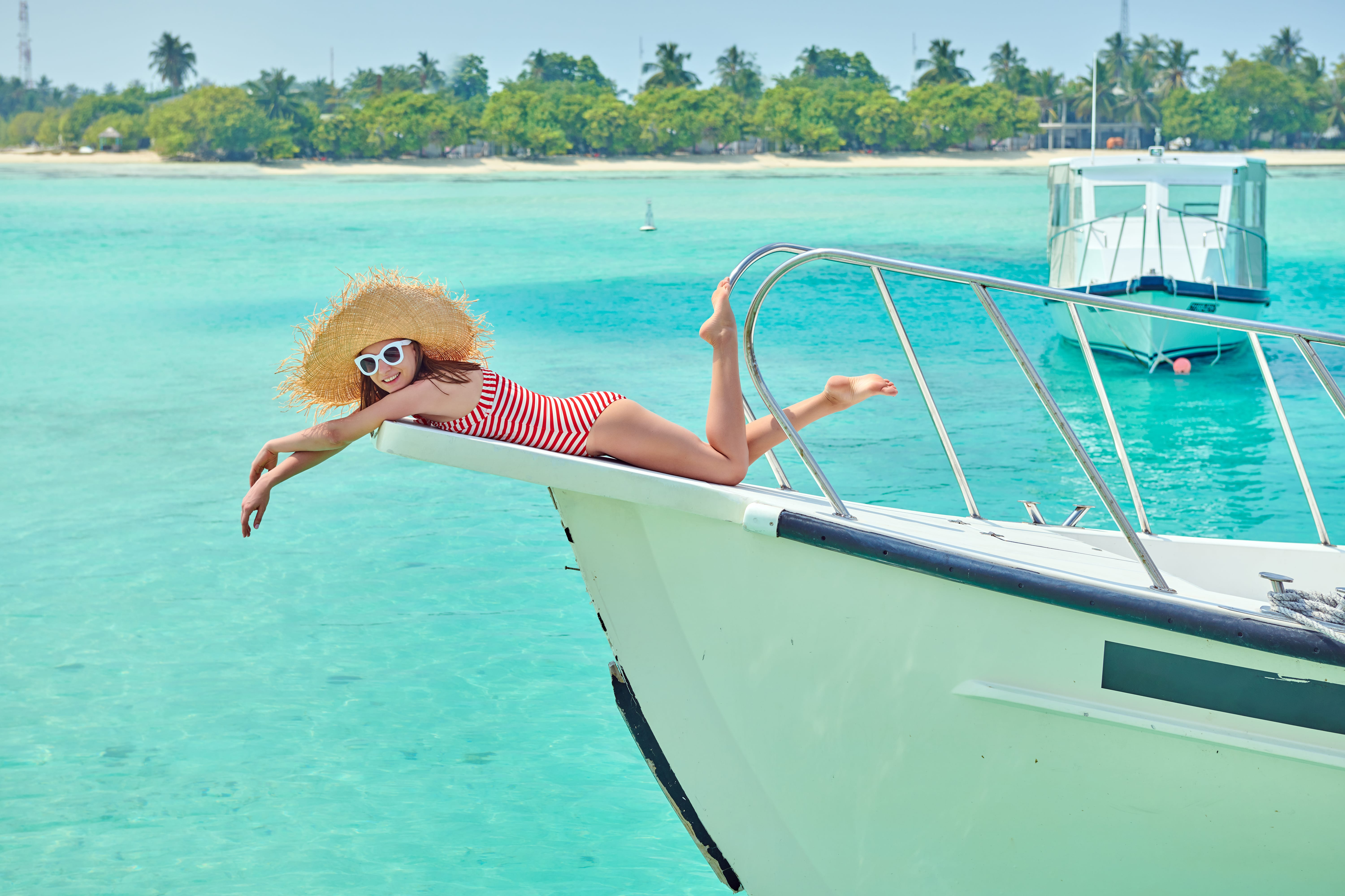 Woman in red striped one-piece swimsuit lying on boat bow. Summer vacation at Maldives.