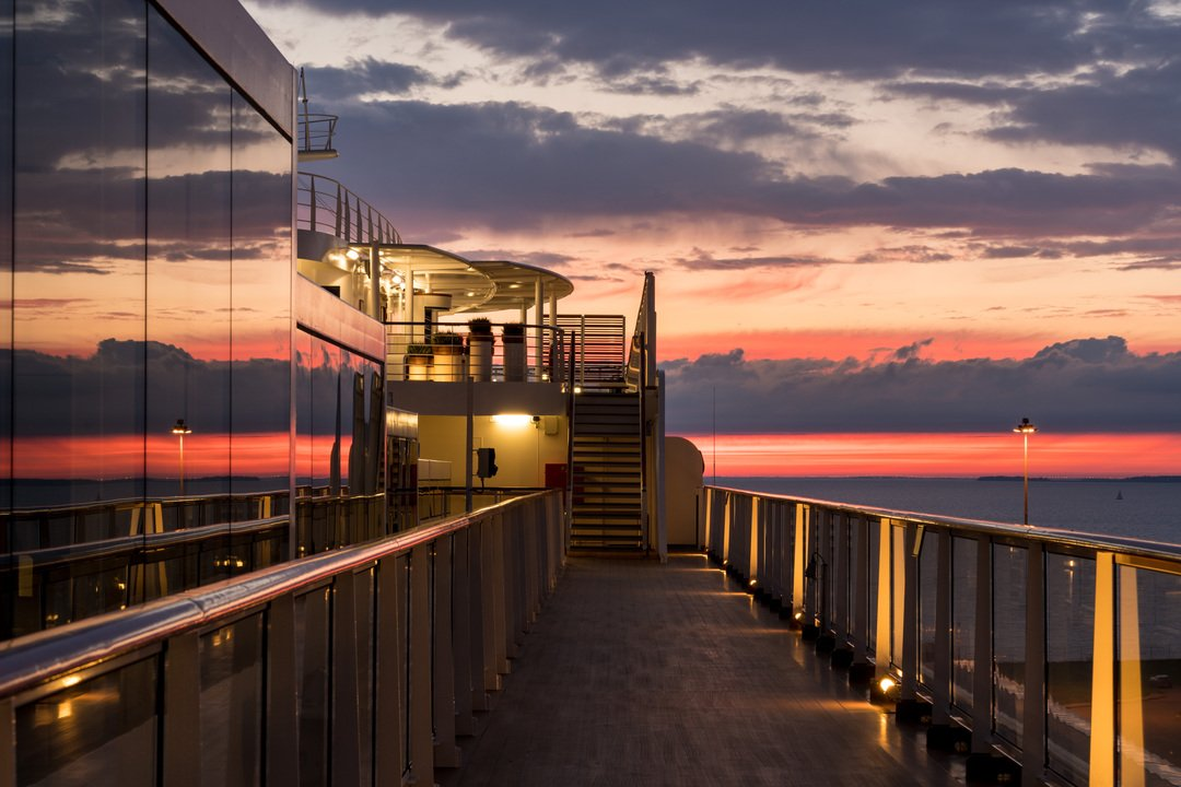 Reflections of the sunset in the windows of a modern cruise ship at dusk